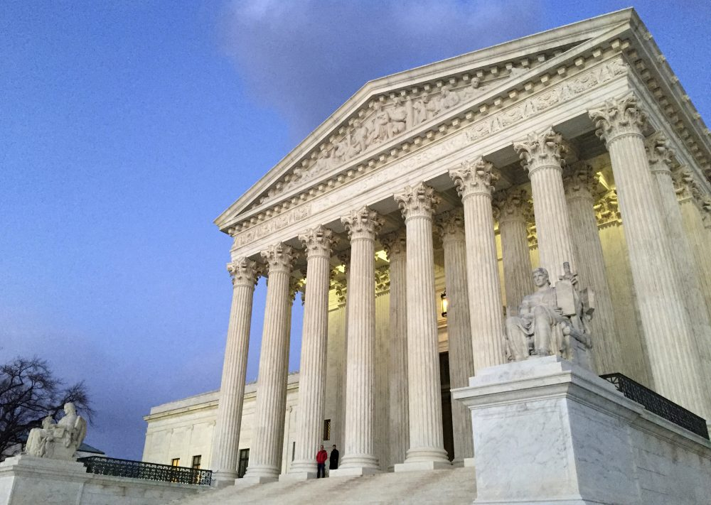 People stand on the steps of the Supreme Court at sunset in Washington in 2016. (Jon Elswick/AP)
