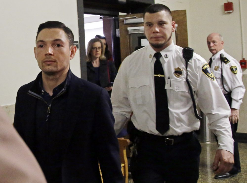 Bryon Hefner, the estranged husband of former Massachusetts Senate President Stan Rosenberg, is escorted out of court after his arraignment at Suffolk Superior Court on April 24, 2018, in Boston. (Elise Amendola/AP)