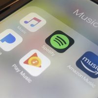 This Sunday, Jan. 28, 2018, photo shows music streaming apps clockwise from top left, Apple, Spotify, Amazon, Pandora and Google on an iPhone in New York. (Jenny Kane/AP)