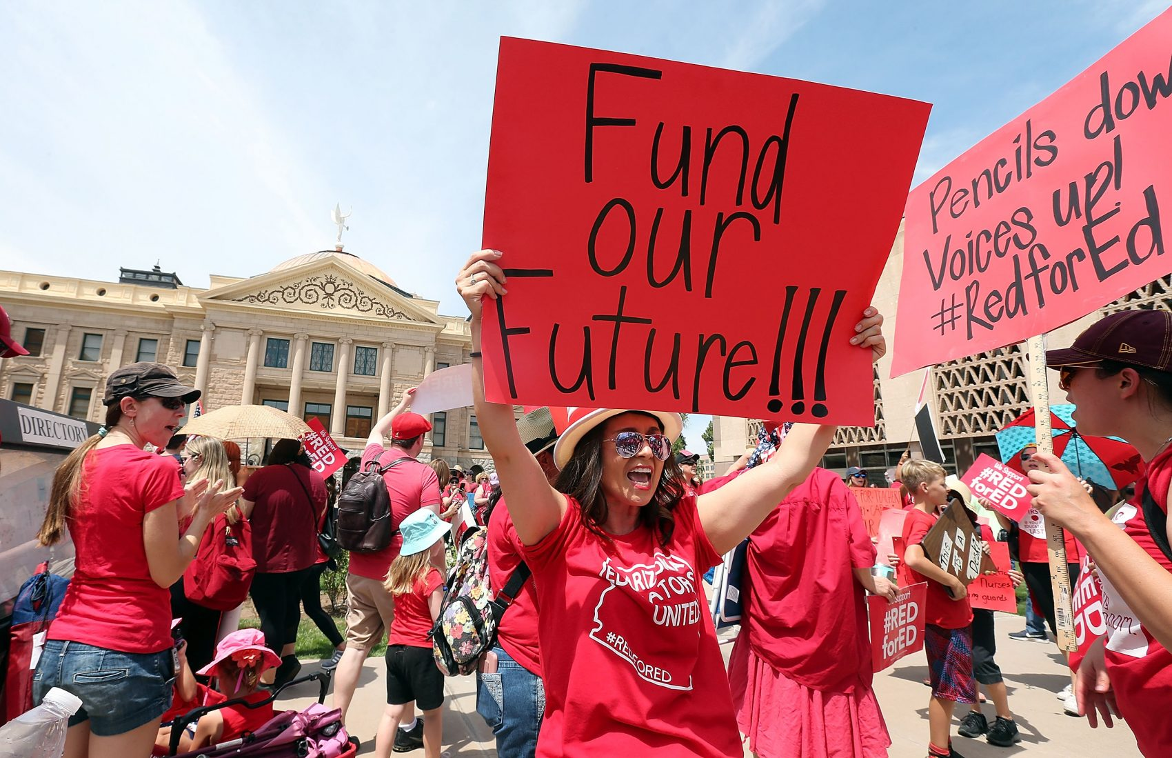 An Arizona teacher holds up a sign in front of the State Capitol during a #REDforED rally on April 26, 2018 in Phoenix, Ariz. Teachers statewide staged a walkout strike on Thursday in support of better wages and state funding for public schools. (Ralph Freso/Getty Images)