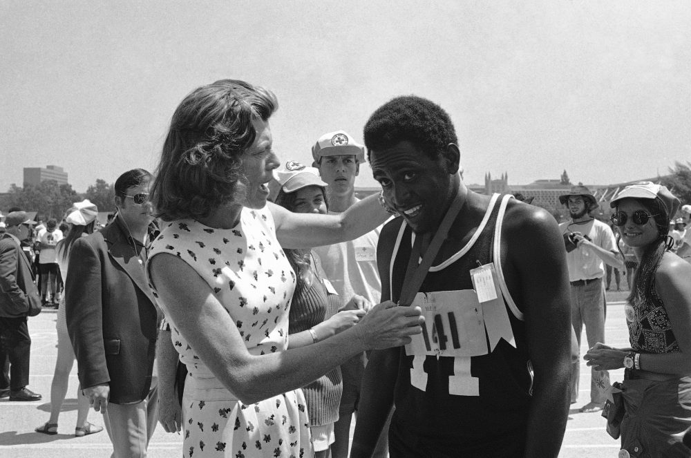 Adonis Brown of Baltimore, Md. smiles as Mrs. Eunice Kennedy Shriver hangs a gold medal around his neck in Aug. 17, 1972 at the International Special Olympics. (Wally Fong/AP)
