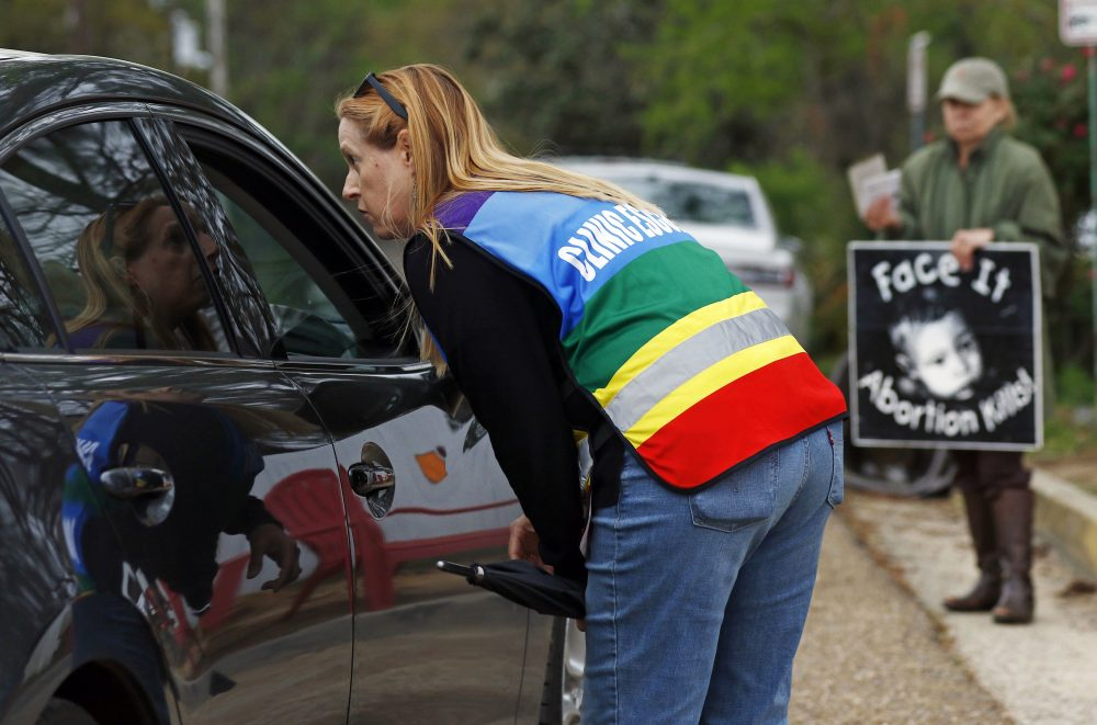 Clinic escort Kim Gibson speaks with driver as they attempt to enter the Jackson Women's Health Organization's clinic parking lot, the only facility in the state that performs abortions, Tuesday, March 20, 2018 in Jackson, Miss. (Rogelio V. Solis/AP)