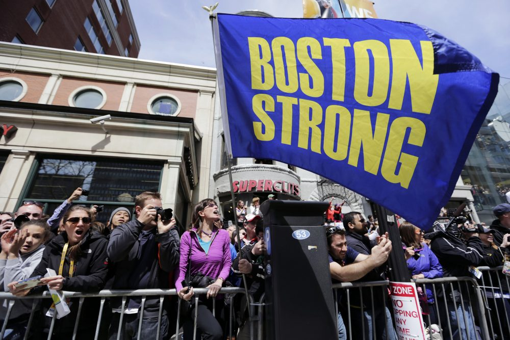 "Race fans with a ""Boston Strong"" flag cheer for competitors near the finish line of the 118th Boston Marathon, Monday, April 21, 2014, in Boston. (Robert F. Bukaty/AP)"