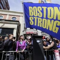 """Race fans with a """"Boston Strong"""" flag cheer for competitors near the finish line of the 118th Boston Marathon, Monday, April 21, 2014, in Boston. (Robert F. Bukaty/AP)"""