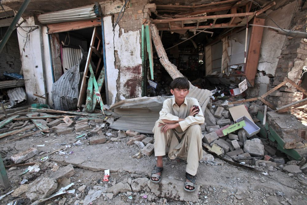In this 2012 file photo, a Pakistani youth sits amid the rubble of offices destroyed in a car bomb explosion in the Pakistani town of Darra Adam Khel in the troubled Khyber Pakhtunkhwa province bordering Afghanistan. (Mohammad Sajjad/AP)