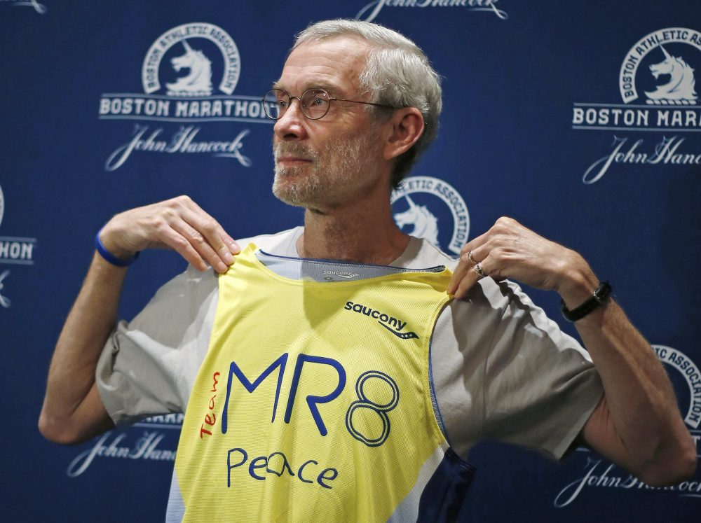 1968 Boston Marathon champion Amby Burfoot holds up a singlet during a news conference in Boston on April 17, 2014. Burfoot will wear it when he runs the Boston Marathon for the Martin Richard foundation MR8. (Elise Amendola/AP)