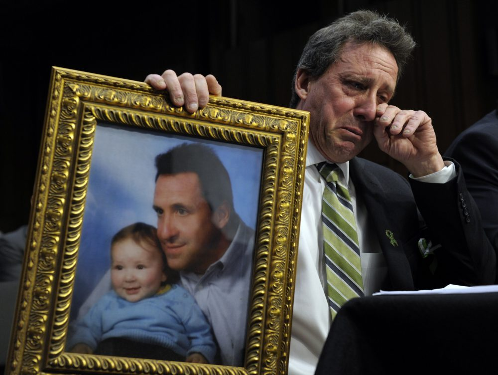 Neil Heslin, the father of a 6-year-old boy who was slain in the Sandy Hook massacre in Newtown, Conn., holds a picture of himself with his son Jesse and wipes his eye while testifying on Capitol Hill in Washington, Wednesday, Feb. 27, 2013. (Susan Walsh/AP)