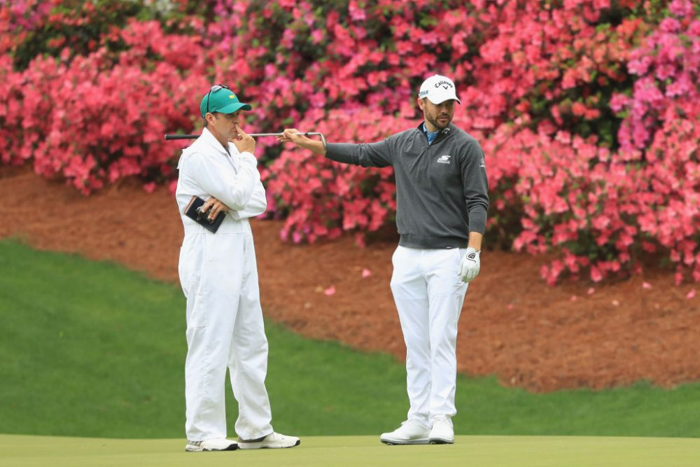 """Wesley Bryan talks with his caddie on the 13th hole during a practice round prior to the start of the 2018 Masters. Presumably, """"dilly dilly"""" was not used during their conversation. (Andrew Redington/Getty Images)"""