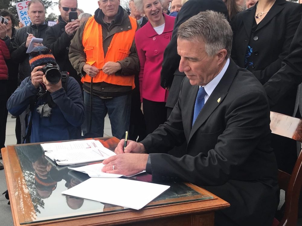 Vermont Gov. Phil Scott signs three pieces of gun control legislation amid boos and cheers on the front steps of the statehouse Wednesday. (Emily Alfin Johnson/VPR)