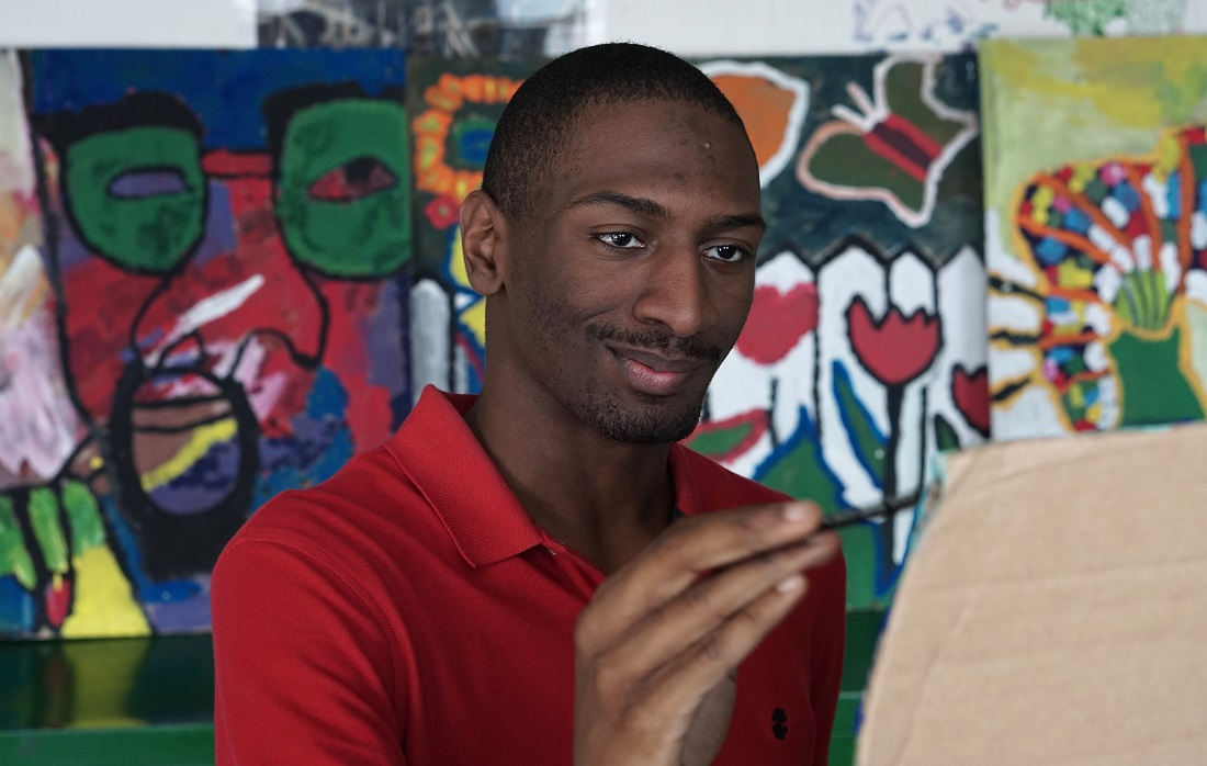 Naieer, one of the young adults profiled in the documentary, paints at the Henderson Inclusion School in Boston. (Courtesy)