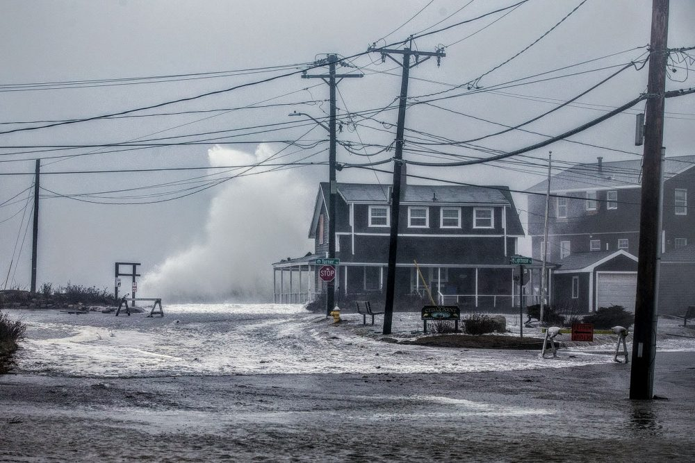 A wave crashes high above a house on Oceanside Avenue in Scituate during a nor'easter on March 3. (Jesse Costa/WBUR)