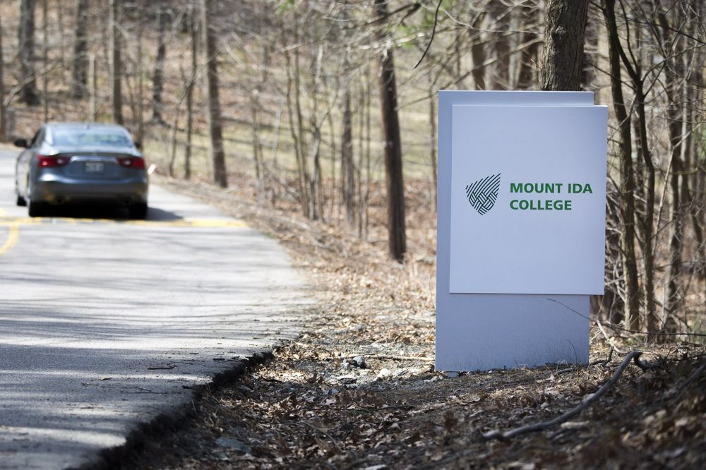 A car drives past the Mount Ida College sign on Carlson Avenue in Newton. (Jesse Costa/WBUR)