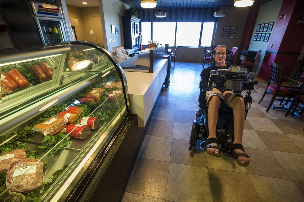 Steve Saling passes by the deli counter in the cafe at the Leonard Florence Center For Living in Chelsea. (Jesse Costa/WBUR)
