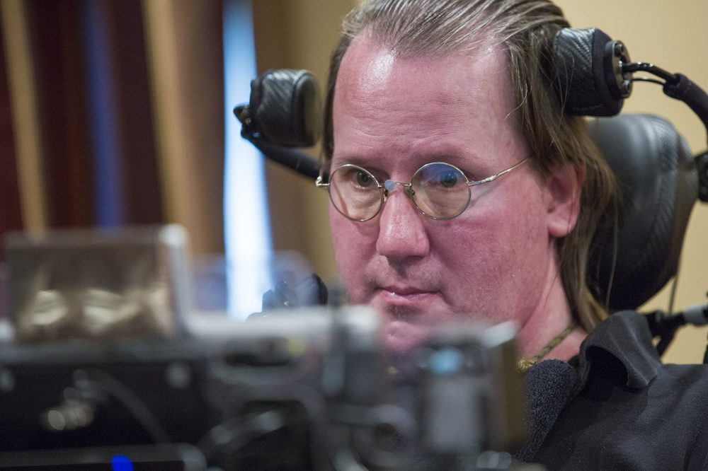 Steve Saling uses a computer with a tiny mouse mounted to the bridge of his glasses to communicate. (Jesse Costa/WBUR)