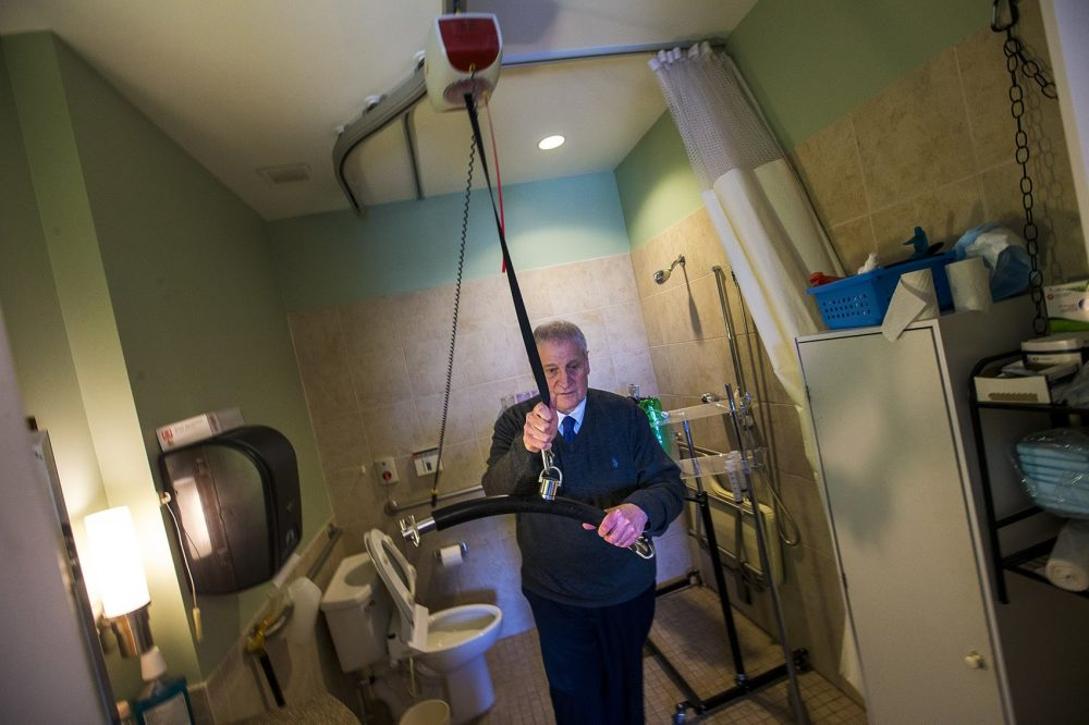 Barry Berman, CEO of Chelsea Jewish Lifecare, which operates the Leonard Florence Center For Living, demonstrates the lift that aides use to get Steve from his bed into the bathroom. (Jesse Costa/WBUR)