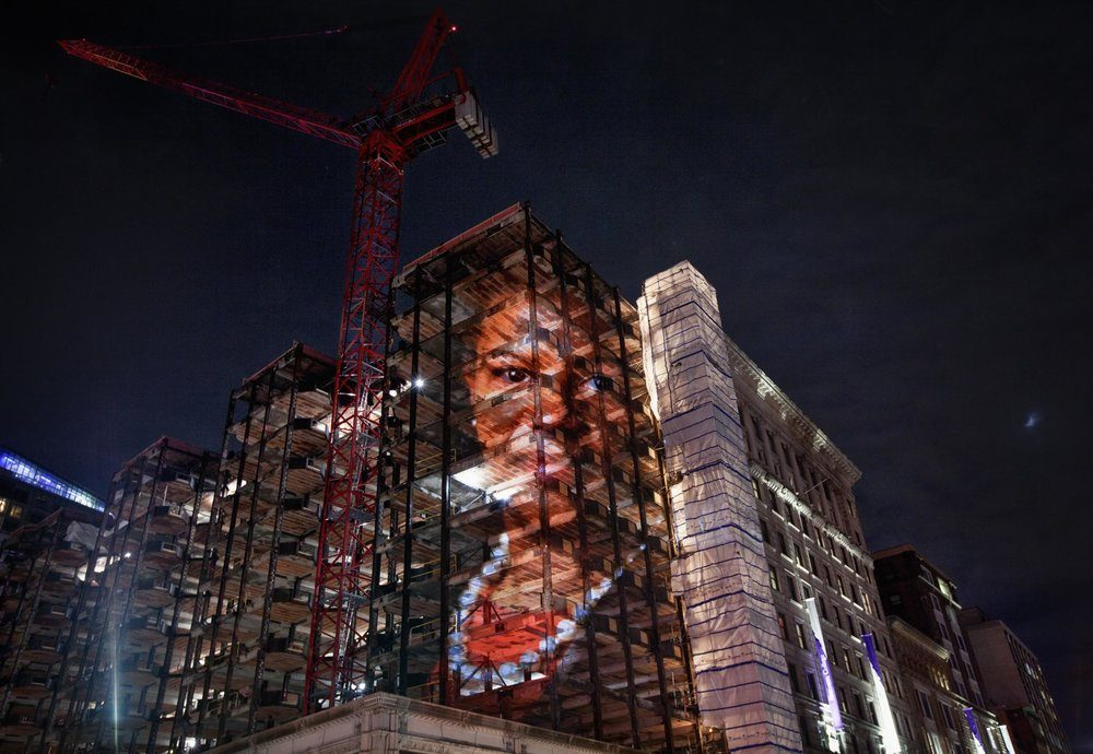 An image of former state Sen. Linda Dorcena Forry projected on a building under construction on Tremont Street. (Courtesy Erik Jacobs)