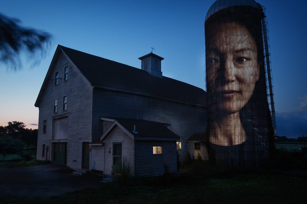 A portrait of Jennifer Hyoje-Ryu Kenty projected onto a barn's silo at Alexander Farm in Winchendon. (Courtesy Erik Jacobs)