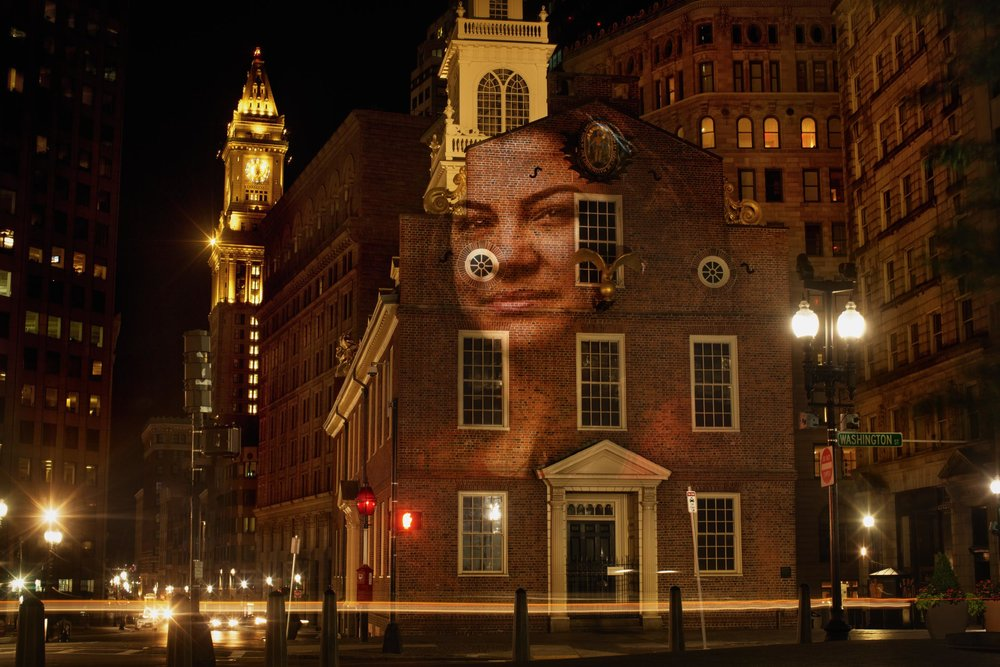 A portrait of Jennis Perez, who is from Cuba, projected on the Old State House in Boston. (Courtesy Erik Jacobs)