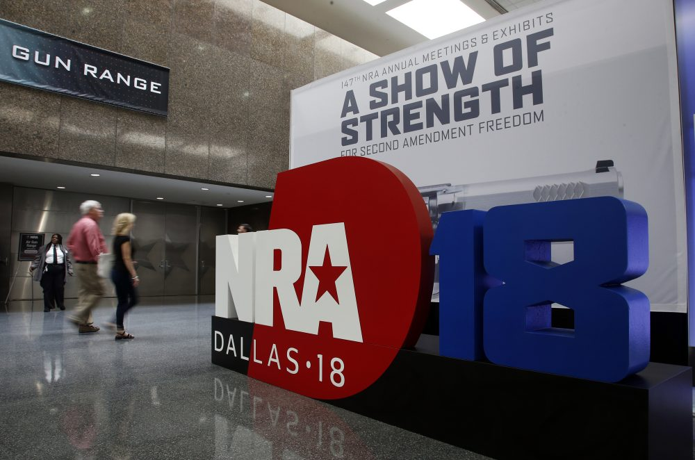 People walk by NRA convention signage in the Kay Bailey Hutchison Convention Center in Dallas, Thursday, May 3, 2018. The convention is scheduled to go through Sunday. (Sue Ogrocki/AP)