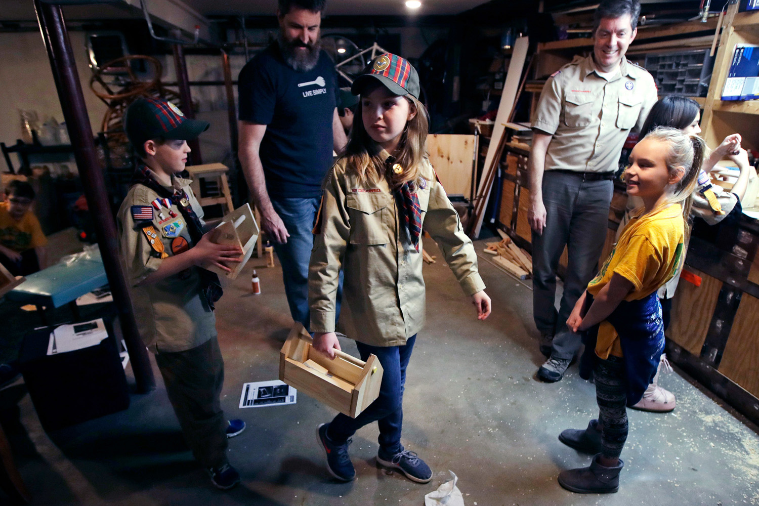 "Tatum Weir, center, carries a tool box she built as her twin brother Ian, left, follows after a Cub Scout meeting in Madbury, N.H. With girls soon entering the ranks, the BSA says that iconic name will change to ""Scouts BSA."" The change will take effect in February 2019. (Charles Krupa/AP File)"