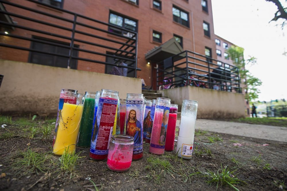Candles sit in front of the Mildred C. Hailey Apartments where the shooting deaths of Christopher Joyce and Clayborn Blair occured Friday night. (Jesse Costa/WBUR)