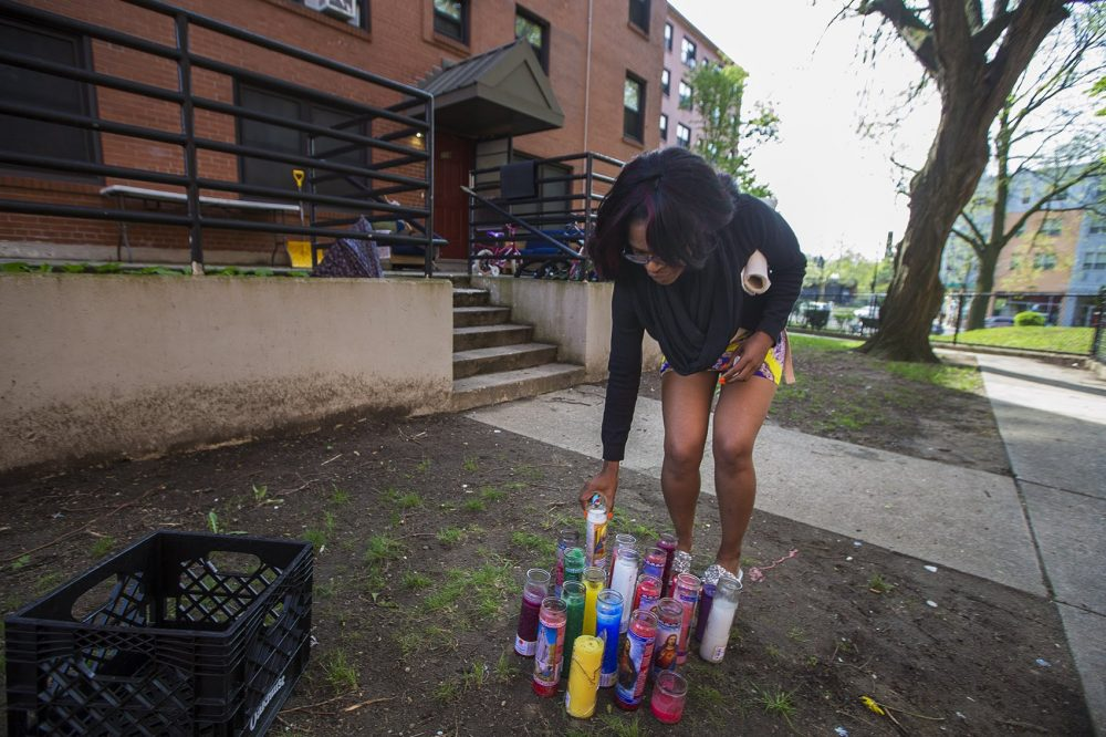 Mildred C. Hailey Apartments resident Anetra Warren places a lit candle at the memorial set up for the shooting deaths of Christopher Joyce and Clayborn Blair. (Jesse Costa/WBUR)