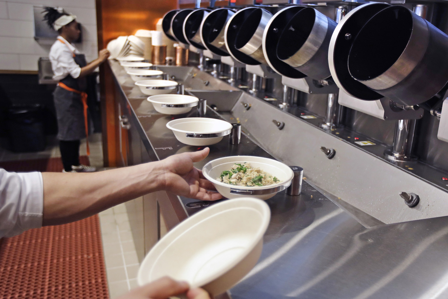 """A worker lifts a lunch bowl off the production line at Spyce, a restaurant which uses a robotic cooking process, in Boston, Thursday, May 3, 2018. Robots can't yet bake a souffle or fold a burrito, but the new restaurant in Boston is employing what it calls a """"never-before-seen robotic kitchen"""" to cook up ingredients and spout them into a bowl. (Charles Krupa/AP)"""