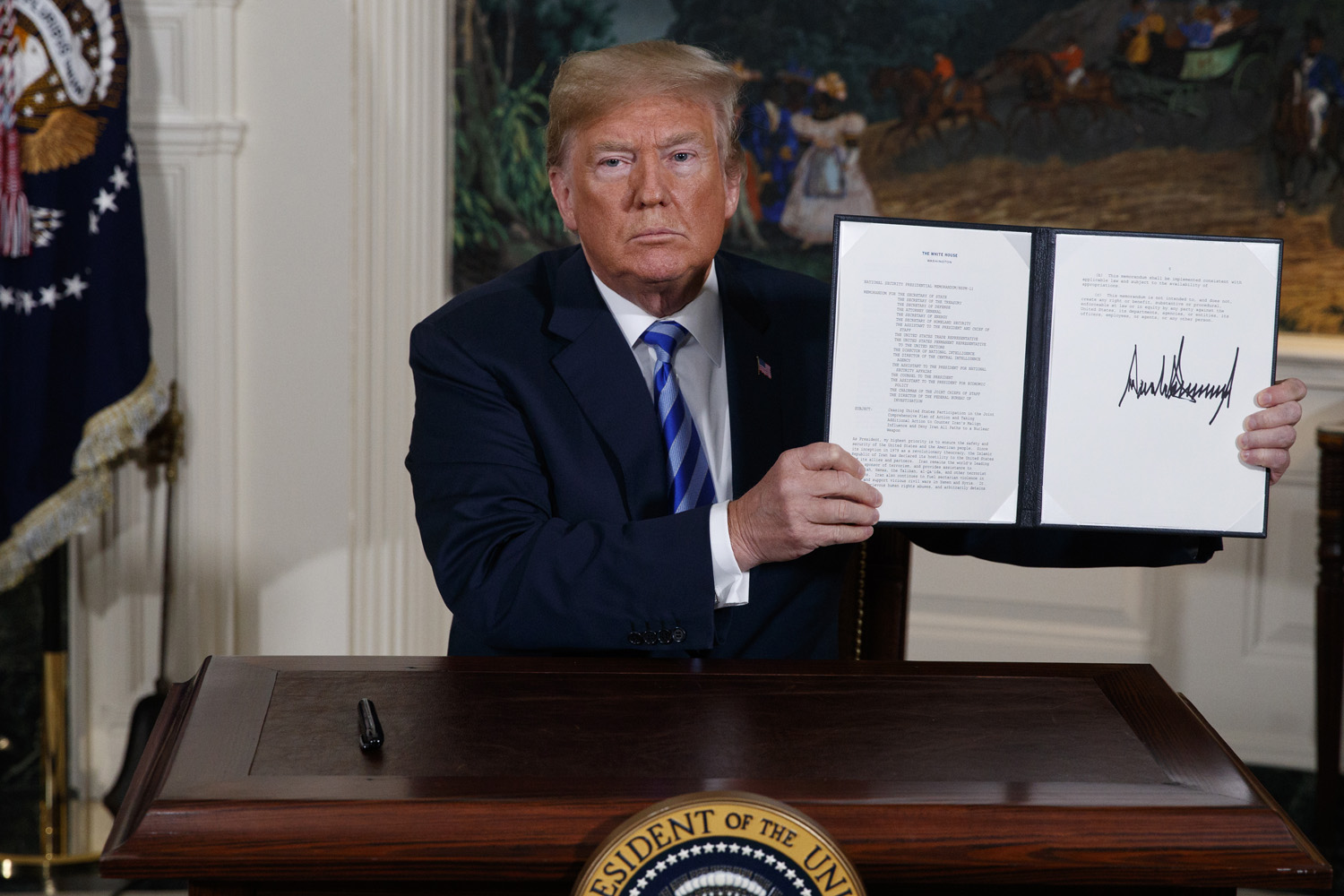 President Trump shows a signed Presidential Memorandum after delivering a statement on the Iran nuclear deal from the White House, Tuesday in Washington. (Evan Vucci/AP)