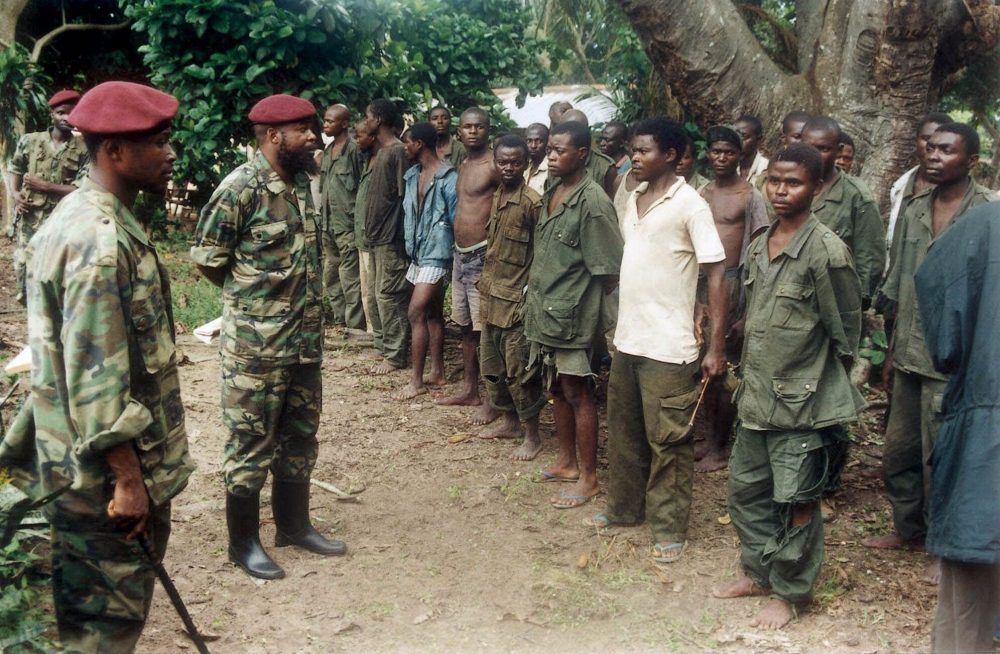 Rebels of the Movement for the Liberation of Congo, in red berets, inspect government prisoners of war in August 2000. (Cranimer Mugerwa/AP)