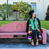 Rosibeth Cuevas, 21, sits on a bench that was dedicated to those who died in a bus crash in Orland, Calif., in 2014. Cuevas is one of the survivors of the crash and is now graduating from Humboldt State University. (Courtesy Sofia Tam)