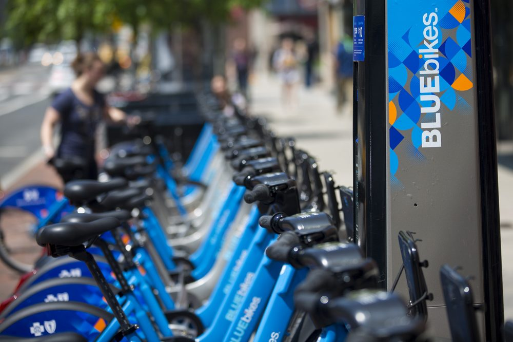 A woman returns a Blue Bike to a station in Kendall Square. (Jesse Costa/WBUR)