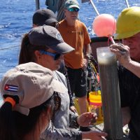 Marine geologist David Hollander (USF, right) instructs Cuban students on sediment core sampling techniques off northwest Cuba. Dr. Greg Brooks (Eckerd College, orange shirt) assists. (Courtesy of C-IMAGE)