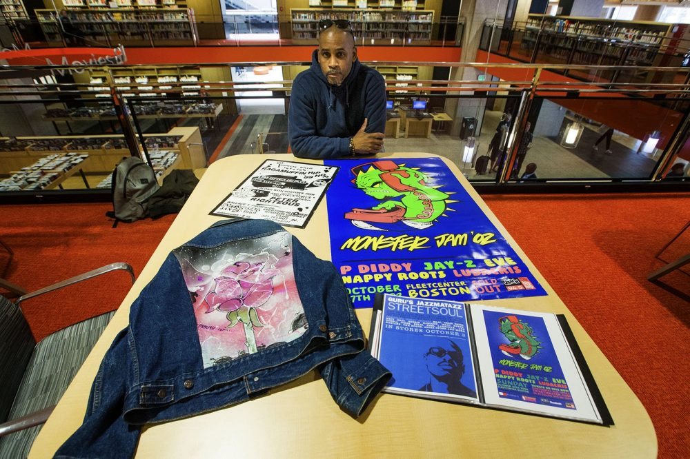 Rob Stull with posters he designed for various Boston hip-hop shows. (Jesse Costa/WBUR)