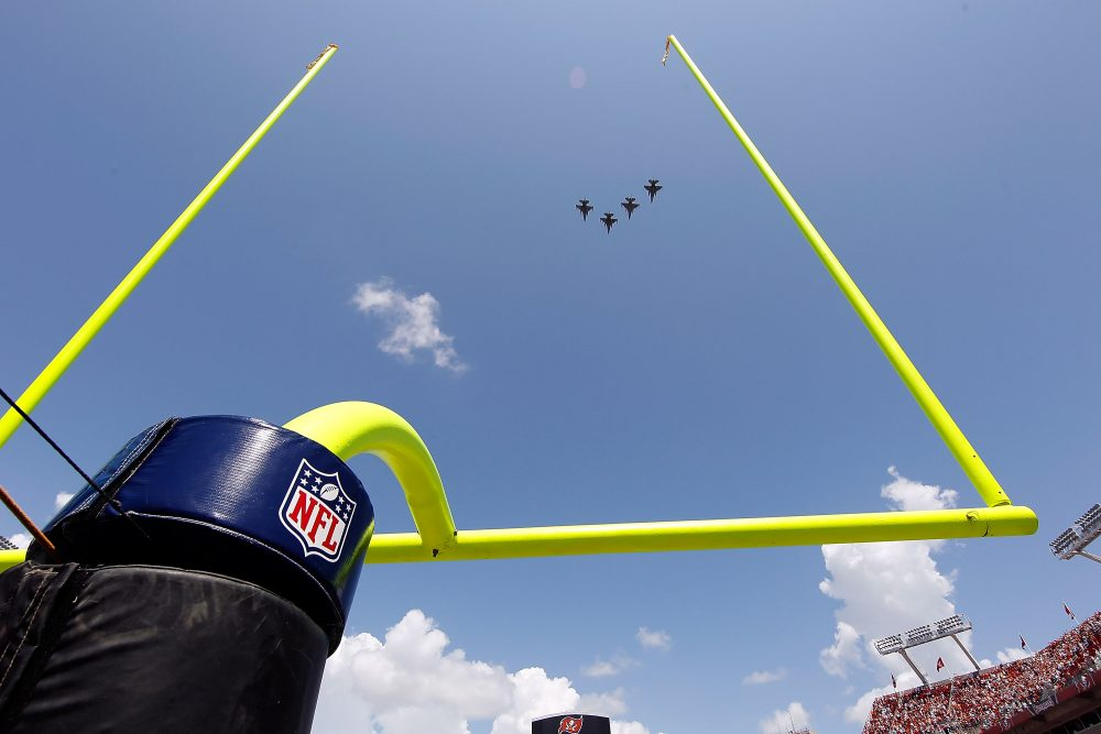 """They were all in on it: NASCAR, MLB, the NBA, the NFL, NHL, MLS, and the NCAA. The military was using sports to sell the business of war,"" Howard Bryant writes. Pictured: Fighter jets fly over Raymond James Stadium just prior to the start of a game between the Tampa Bay Buccaneers and the Cleveland Browns. (J. Meric/Getty Images)"