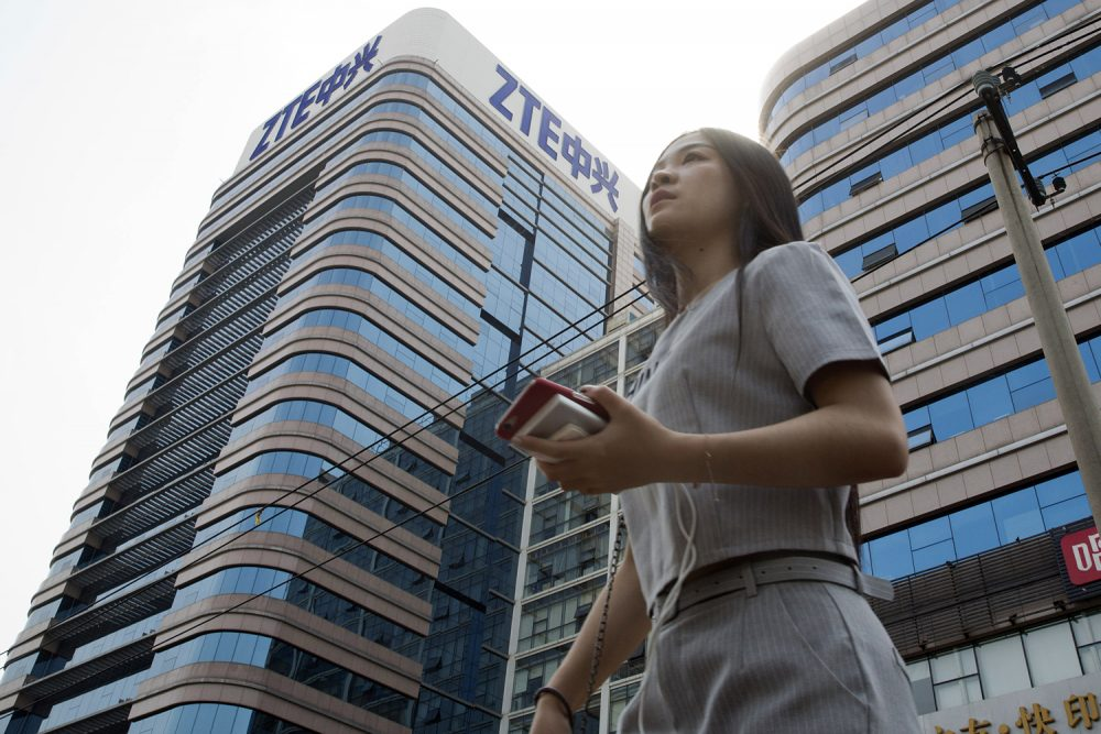 In this May 8, 2018, photo, a woman passes by a ZTE building in Beijing, China. (Ng Han Guan/AP)
