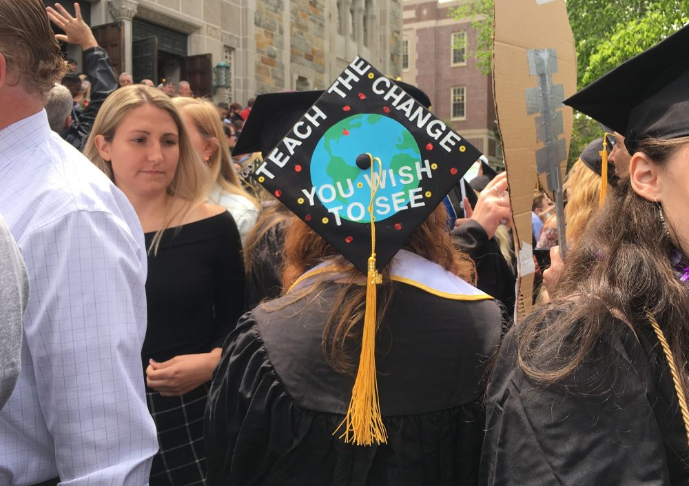 A freshly-graduated Wheelock College alumnae stands outside following the school's final undergraduate commencement. (Lisa Creamer/WBUR)