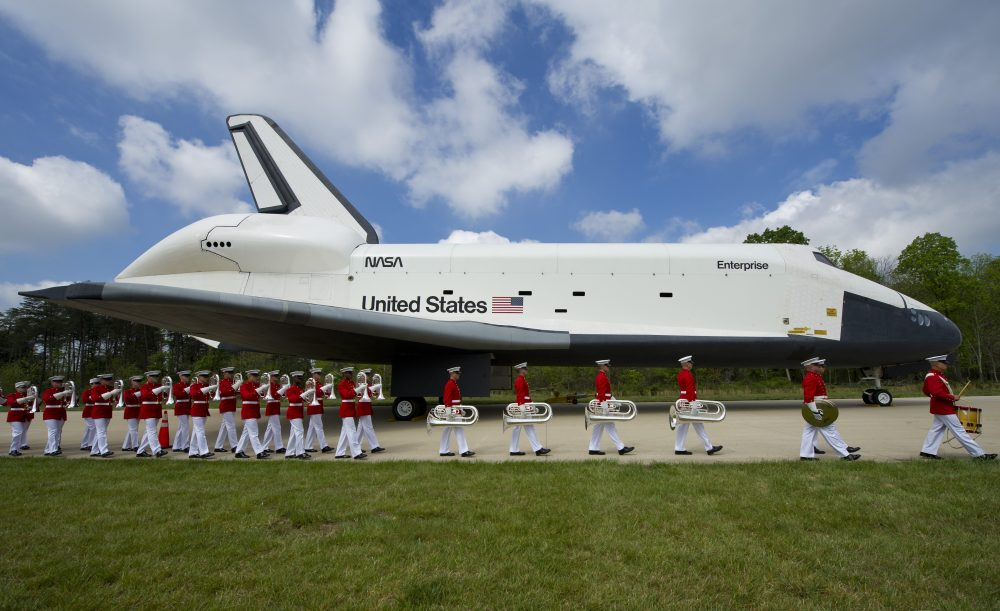 In this handout provided by NASA, U.S. Marine Corp Drum and Bugle Corps and Color Guard march past the space shuttle Enterprise, seen as the at the Steven F. Udvar-Hazy Center April 19, 2012, in Chantilly, Virginia. (Carla Cioffi/NASA via Getty Images)