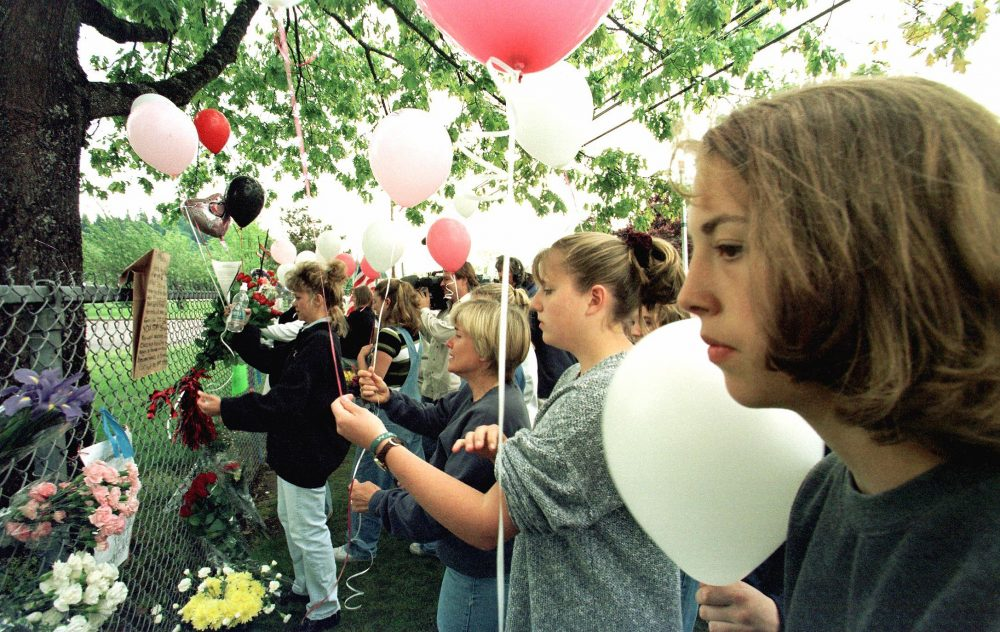 Residents of Springfield, Ore., gather near the fence of Thurston High School on May 22, 1998, to pay respect to those who died in the previous day's shooting in the school's cafeteria. (Hector Mata/AFP/Getty Images)