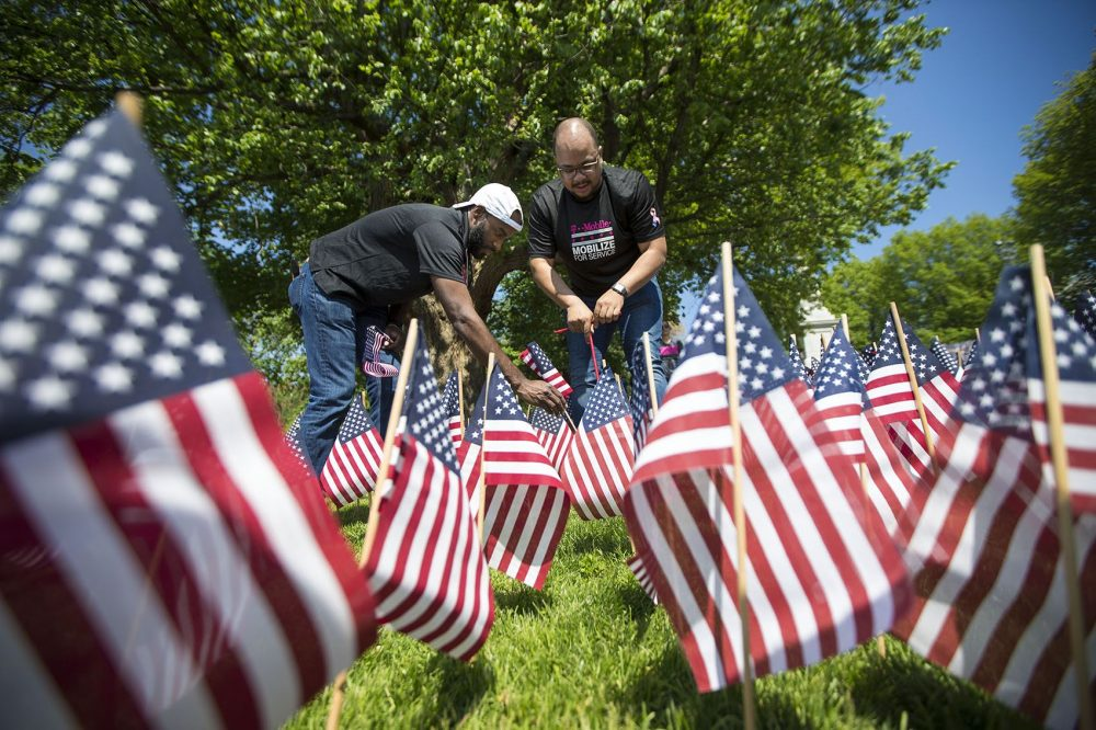 Volunteers Mike Free, left, and Billy Watkins help plant over 37,000 flags in the ground for the 2018 annual Memorial Day flag garden in the Boston Common. (Jesse Costa/WBUR)