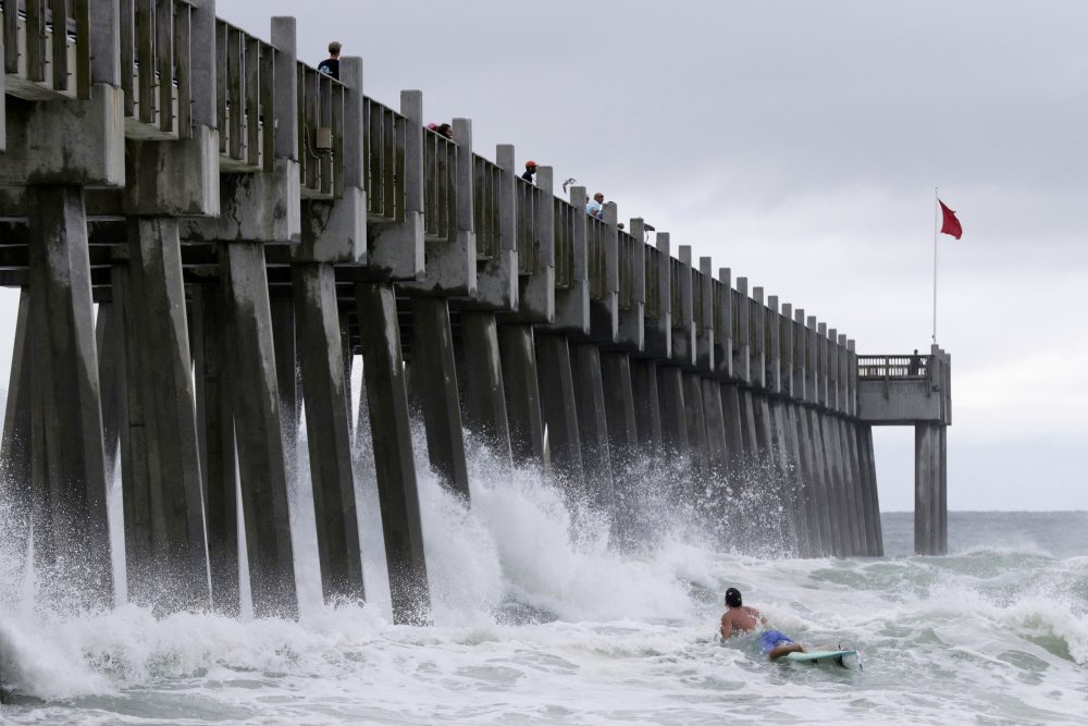 A surfer makes his way out into the water as a subtropical approaches on Monday, May 28, 2018, in Pensacola, Fla. The storm gained the early jump on the 2018 hurricane season as it headed toward anticipated landfall sometime Monday on the northern Gulf Coast, where white sandy beaches emptied of their usual Memorial Day crowds. (Dan Anderson/AP)