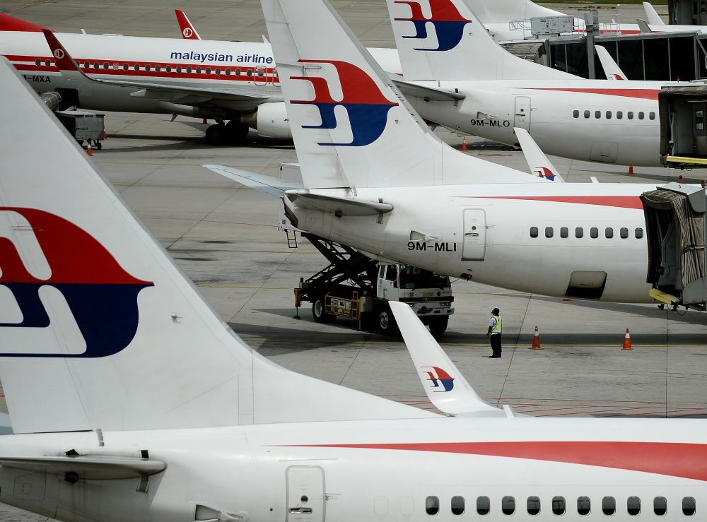 Malaysia Airlines ground staff walk past Malaysia Airlines aircraft parked on the tarmac at the Kuala Lumpur International Airport in Sepang in 2016. (Manan Vatsyayana/AFP/Getty Images)
