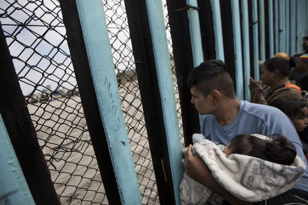In this April 29, 2018 file photo, a member of the Central American migrant caravan, holding a child, looks through the border wall toward a group of people gathered on the U.S. side, as he stands on the beach where the border wall ends in the ocean, in Tijuana, Mexico, Sunday, April 29, 2018 (AP Photo/Hans-Maximo Musielik, File)
