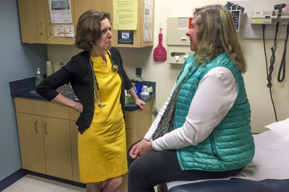 "During a routine primary care checkup, Dr. Rebecca Lee opens a difficult conversation with Stacey Regal-O'Hare, who has a serious illness: ""What are your goals for the end of life?"" (Martha Bebinger/WBUR)"