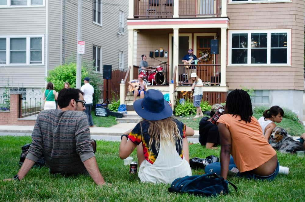 People watch musicians perform on on Lamartine Street at the JP Porchfest in 2017. (Elizabeth Gillis/WBUR)