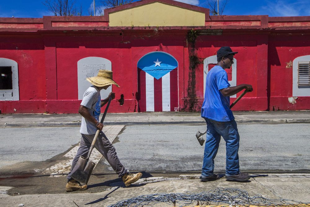 Beach workers walk along a street in Punta Santiago. (Jesse Costa/WBUR)