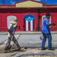 Beach workers walk along a street in Punta Santiago. (Jesse Costa/WBUR)