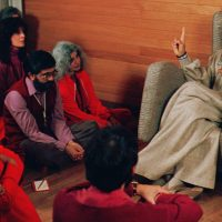 Bhagwan Shree Rajneesh, right, speaks with his disciples in this undated photo in Rajneeshpuram, Ore. (Jack Smith/AP)