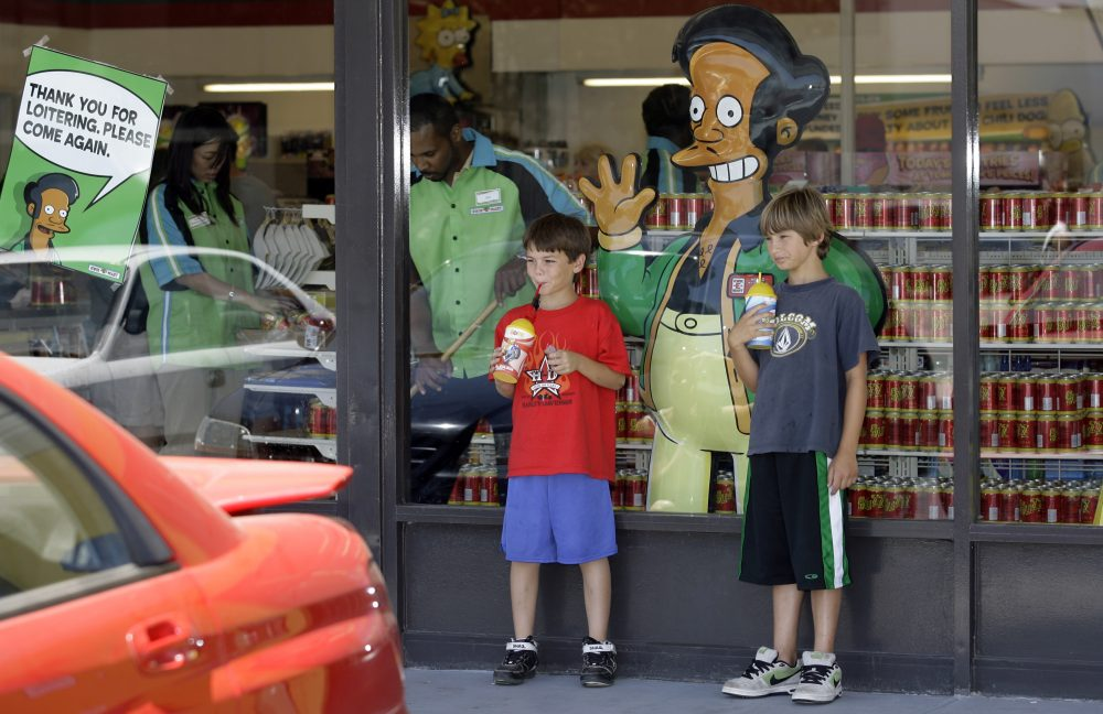 "Children pause next top a poster with ""The Simpsons"" character Apu Nahasapeemapetilon, Jr., outside the 7-Eleven 'Kwik-E-Mart' in Burbank, Calif. Monday, July 2, 2007. (Damian Dovarganes/AP)"