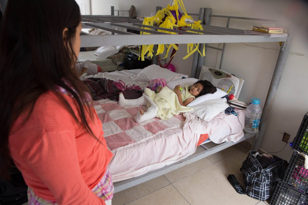 In this Dec. 15, 2015, photo, Marleny Gonzalez, left, looks at her 4-year-old daughter, Jenifer at a shelter in Reynosa, Mexico, where they are living after trying to cross into the U.S. Gonzalez said her daughter suffered two broken legs when a truck they were traveling in overturned on the journey from Guatemala. (Seth Robbins/AP)