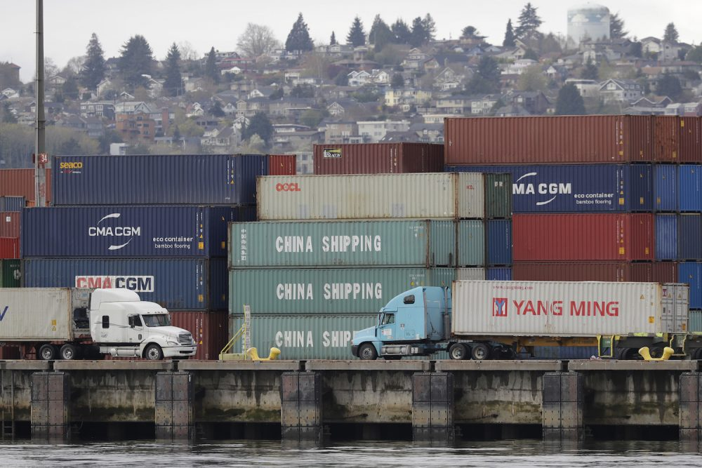 """Trucks pass by cargo containers labeled """"China Shipping,"""" Friday, April 6, 2018, at the Port of Seattle.  (Ted S. Warren/AP)"""